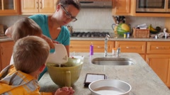 Mother making cake with little boys in the kitchen dolly shot Stock Footage
