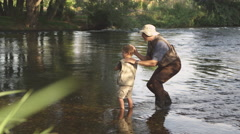Grandfather teaching grandson to fish Stock Footage