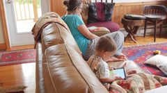 Mother reads an ebook while toddler plays on iPad Stock Footage