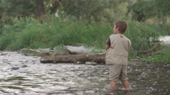 Slow motion of little boy fishing in creek Stock Footage