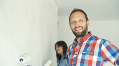 Couple painting wall at their new home, portrait of happy man Stock Footage