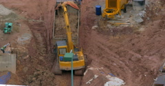 In Kuala Lumpur, Malaysia in the pit excavator pours earth into a truck Stock Footage