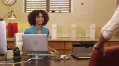 Woman greeting two customers in office Stock Footage
