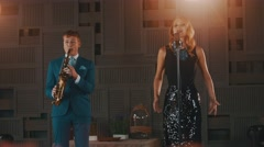 Jazz vocalist in glare dress and saxophonist in blue suit perform on stage. Duet Stock Footage