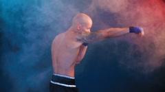 Muscular kickbox or muay thai fighter punching in smoke Stock Footage