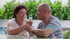 Happy caucasian elderly couple drinking champagne clink on the villa pool Stock Footage