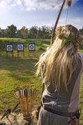 Medieval woman archer shoot at a target Stock Photos