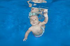 Infant swim under water in the pool Kuvituskuvat