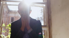 The sad young man in a suit sitting on a windowsill, suffers. The sun shines in Stock Footage