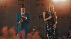 Jazz vocalist in glare dress dance perform with saxophonist in blue suit. Stage Stock Footage