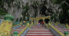 Young woman at Batu Caves, Malaysia climbs the stairs and takes pictures on Stock Footage