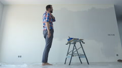 Young man having shoulder pain while painting wall at his new home Stock Footage