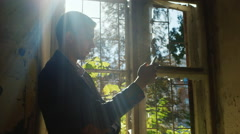 Sad young man standing at the window in an abandoned house. He looks at the Stock Footage
