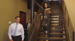 Three office workers near staircase talking about work Stock Footage