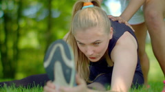 Girl doing stretching exercise outdoor. Stretching exercise at park Stock Footage