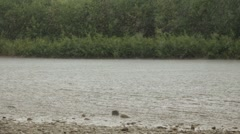 Heavy rainfall hitting the river surface. Heavy rain on a background of a river Arkistovideo