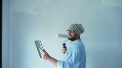 Young, hipster man chatting on tablet while painting wall at his new home  Stock Footage