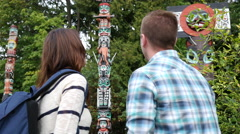 Couple looking at totem poles Stock Footage