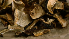 Dried mushrooms falling on parchment. Slow motion video. Stock Footage