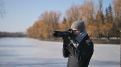 Young man Photographer With professional Camera Equipped in Black Parka Taking Stock Footage