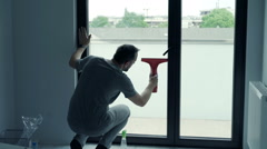 Young man cleaning window at home Stock Footage