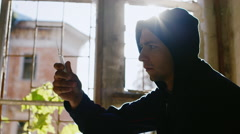 To overcome drug addiction. A young man throws a syringe, sitting at a window in Stock Footage