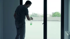 Young man with detergent cleaning window at home Stock Footage
