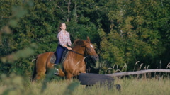 Beautiful girl riding a horse in countryside in slow motion Stock Footage