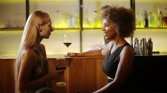 Two girls chatting and drinking wine at the luxury bar. At background barman Stock Footage