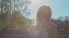 Happy Smiling Girl Using SmartPhone in City Park Sitting on the Bench Stock Footage