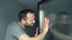 Unhappy, angry man cleaning window at home Stock Footage