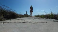 Girl walking towards lighthouse on Klein Curacao Stock Footage