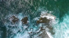 Aerial of rocks getting slammed by waves in ocean at Klein Curacao Stock Footage
