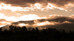 Mountain silhouette and clouds in the early morning sun Stock Footage