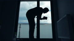 Silhouette of young man cleaning window at home Stock Footage
