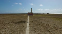 Aerial fly over of girl walking towards abandoned lighthouse at Klein Curacao Stock Footage