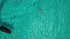 Aerial of jet ski circling girl swimming in water at Klein Curacao Stock Footage