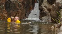 Little Blond Girl in Arm-hands Swims at Waterfall Stock Footage
