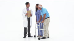 Doctor and nurse talk to elderly patient on walker and passing over medications Stock Footage