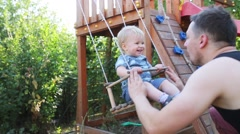 One years-old baby boy with blue eyes play on the swing outdoor Stock Footage