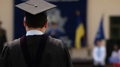 Man in academic dress excited about receiving diploma at graduation ceremony Stock Footage