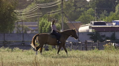 Cowgirl riding a horse in countryside in slow motion Stock Footage