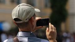 Male passer-by filming accident site on phone, defocused crowd of bystanders Stock Footage