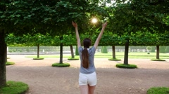 Tourist girl walk in garden, rise hands touch leaves slightly, slow motion Stock Footage