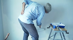 Hipster man having back pain while painting wall at his new home Stock Footage