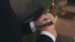Saxophonist in jacket sitting on chair with golden saxophone. Jazz. Elegance Stock Footage