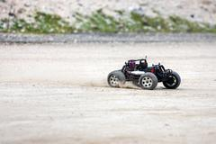 Radio controlled car model in race quickly moving on the sandy road Stock Photos