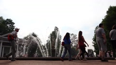 Tourists pass by antique Eva fountain enjoy sightseeing in Peterhof park Stock Footage