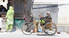 Poor man in a wheelchair with his hand out asking for money to life. India Stock Footage