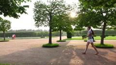 Tourist girl walk against sunshine in Peterhof Upper Gardens, slow motion Stock Footage